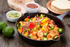 Shrimp Fajitas In Cast Iron Skillet. Shrimp fajitas with bell pepper, onion, and jalapeno in cast iron skillet ready to be served. Guacamole, salse, and Stock Images