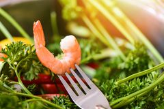 Shrimp on fork / Cooked seafood shrimps prawns ocean gourmet dinner in fork. With herbs and spices parsley green vegetable background stock photo