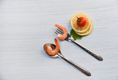 Shrimp on fork and spoon / Cooked seafood shrimps prawns ocean gourmet dinner and tomato lemon. On white table background stock images