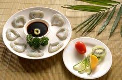 Shrimp and fresh fruit. Plates of shrimp and fresh fruit including kiwi and tomatoes Royalty Free Stock Photography