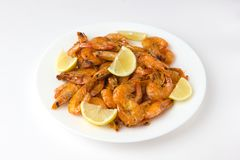 Fried prawns on a white plate. Shrimp fried in a frying pan with butter and garlic Stock Images