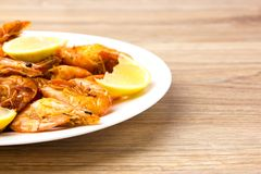 Fried shrimps with lemon. Shrimp fried in a frying pan with butter and garlic Royalty Free Stock Image