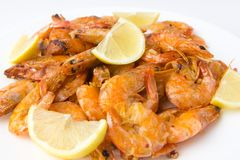 Fried prawns on a white plate. Shrimp fried in oil with garlic and lemon on a plate Royalty Free Stock Photos