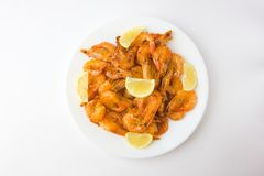 Fried prawns on a white plate. Shrimp fried in oil with garlic and lemon on a plate Stock Photography