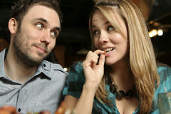 Shrimp Is Good. Close up of a young couple dining at a restaurant. Woman eating shrimp. Shallow dof with background and foreground blurred Stock Photography
