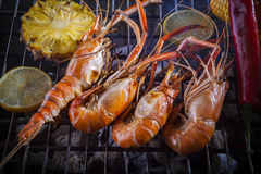 Shrimp grilled on barbeque charcoal oven with lemon pineapple re Royalty Free Stock Photo