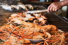 Shrimp grilled in grilling basket. Grilled shrimps on the flaming grill, seafood royalty free stock photos