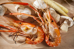 Shrimp grilled with mushroom and corn on wood plate Stock Images