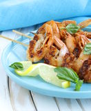 Shrimp grilled on wooden skewers with lemon Stock Images