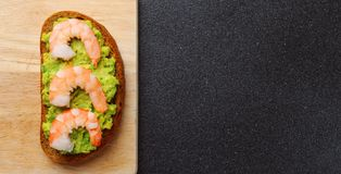 Shrimp and guacamole with bread on dark background royalty free stock image