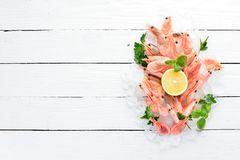 Shrimp with ice and lemon. Seafood. On a white wooden background. Top view. Free copy space royalty free stock photos