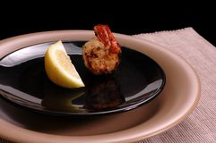 Shrimp and lemon on black plate. Sauted shrimp with lemon on black plate Royalty Free Stock Photo