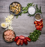 Shrimp and mussels in metal bowls with spices onion pepper tomatoes and herbs lined circle frame wooden background top view Stock Photos