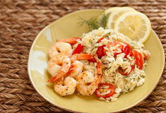 Shrimp and orzo with tomatoes. A light summer meal of shrimp, orzo, tomatoes, dill, feta cheese, and lemons sits on a light green plate Royalty Free Stock Image