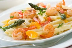 Shrimp Pasta. Closeup of plate of Shrimp Penne (tube-shaped pasta) with asparagus, bell pepper, origan and creamy Alfredo sauce . Shallow DOF Royalty Free Stock Photos