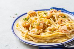 Shrimp pasta with cream and herbs in white plate, copy space