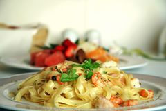 Shrimp pasta with a fruit salad dessert Royalty Free Stock Photography