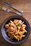 Shrimp penne with sun dried tomatoes and basil in creamy mozzarella sauce. Pasta with shrimps in bowl on wooden table. Overhead, vertical Stock Photos