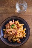 Shrimp penne with sun dried tomatoes and basil in creamy mozzarella sauce. Pasta with shrimps in bowl on wooden table. Overhead, vertical Royalty Free Stock Photo