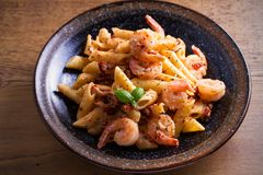 Shrimp penne with sun dried tomatoes and basil in creamy mozzarella sauce. Pasta with shrimps in bowl on wooden table. Horizontal Royalty Free Stock Photography