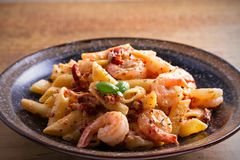 Shrimp penne with sun dried tomatoes and basil in creamy mozzarella sauce. Pasta with shrimps in bowl on wooden table. Horizontal Royalty Free Stock Image