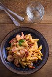 Shrimp penne with sun dried tomatoes and basil in creamy mozzarella sauce. Pasta with shrimps in bowl on wooden table. Overhead, vertical Royalty Free Stock Images
