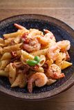 Shrimp penne with sun dried tomatoes and basil in creamy mozzarella sauce. Pasta with shrimps in bowl on wooden table. Vertical Royalty Free Stock Photography