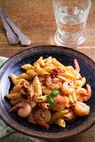 Shrimp penne with sun dried tomatoes and basil in creamy mozzarella sauce. Pasta with shrimps in bowl on wooden table. Vertical Stock Images
