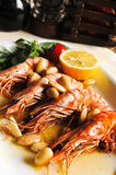 Shrimp on a platter with lemon green beans. Large cooked shrimp on a platter with lemon green beans and tomatoes in a restaurant stock photo