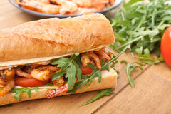 Shrimp Po-Boy Sandwich. With Rocket and Tomato on Wooden Table Stock Photography