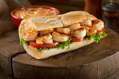 Shrimp Po Boy Sandwich. A delicious home made grilled shrimp Po Boy sandwich on baguette dressed with lettuce, tomato, and remoulade Royalty Free Stock Images