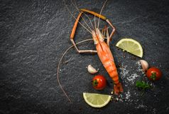 Shrimp prawn cooked shellfish seafood with lemon tomato herbs and spices on dark stock photography