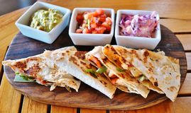 Shrimp quesadillas with guacamole and pico de gallo. On a wooden platter royalty free stock photography