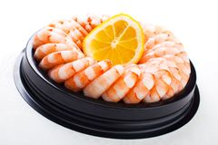 Shrimp ring. On plastic platter with slice of lemon , white background stock photo