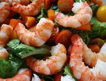 Shrimp Salad. Closeup of nice big shrimp over a bed of leaf lettuce, orange peppers, and red and yellow cherry tomatoes stock photos