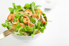 Shrimp salad with cherry tomatoes in bowl. On white background with a glass of water. Copy space Stock Photo