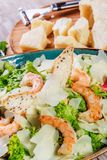 Shrimp salad with parmesan cheese, croutons, tomatoes, mixed greens, lettuce and glass of wine. On wooden background Stock Photos