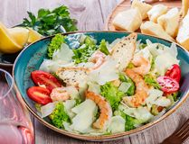 Shrimp salad with parmesan cheese, croutons, tomatoes, mixed greens, lettuce and glass of wine on wooden background. Shrimp salad with parmesan cheese, croutons Stock Photo