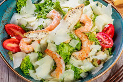 Shrimp salad with parmesan cheese, croutons, tomatoes, mixed greens, lettuce and glass of wine on wooden background Royalty Free Stock Image