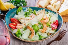Shrimp salad with parmesan cheese, croutons, tomatoes, mixed greens, lettuce and glass of wine on wooden background. Healthy food Royalty Free Stock Image