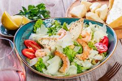 Shrimp salad with parmesan cheese, croutons, tomatoes, mixed greens, lettuce and glass of wine on wooden background. Shrimp salad with parmesan cheese, croutons Stock Photography