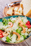 Shrimp salad with parmesan cheese, croutons, tomatoes, mixed greens, lettuce and glass of wine on wooden background. Top view Stock Photos