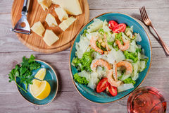Shrimp salad with parmesan cheese, croutons, tomatoes, mixed greens, lettuce and glass of wine on wooden background. Top view Stock Images