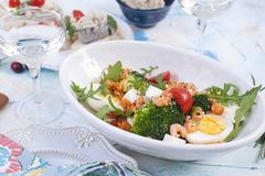 Shrimp salad and vegetables in a white plate and a glass of wine, meat on a wooden board. stock photos
