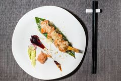 Shrimp and salmon uramaki with bittersweet sauce. Japanese fusion cousine stock image