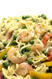 Shrimp scampi. Linguini pasta with garden peas red yellow peppers garlic butter sauce in pan Royalty Free Stock Photos