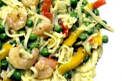 Shrimp scampi. Linguini pasta with garden peas red yellow peppers garlic butter sauce in pan Royalty Free Stock Images