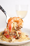 Shrimp Scampi. A delicious shrimp scampi pasta dish along with a glass of pinot grigio white wine.  Shallow depth of field with focus on the fork and shrimp Stock Photos