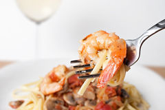 Shrimp Scampi. A delicious shrimp scampi pasta dish along with a glass of pinot grigio white wine.  Shallow depth of field with focus on the fork and shrimp Royalty Free Stock Image