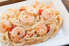 Shrimp Scampi. Made with linguini, diced tomatoes, butter, garlic, parsley and herbs. Served on stacked white and brown plates. Shot in natural light. Selective Stock Image